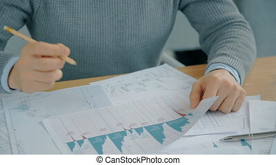 Close up hands of financial analytic working on graphs in the office.