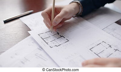 Close up hands of male architect correcting house blueprint.
