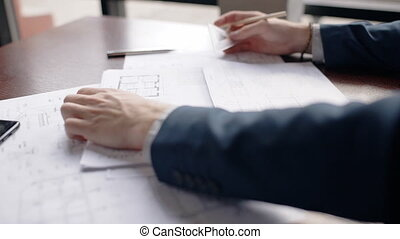 Close up hands of male architect making hause blueprint in office.