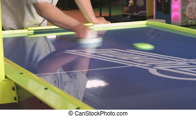 Close-up hands of man playing in an air hockey