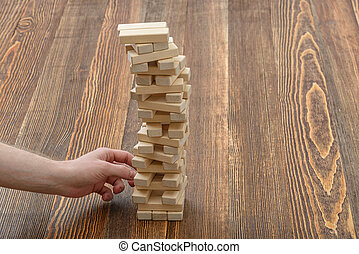 Close-up hands of man pulls out wooden bricks