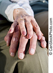 Close-up hands of senior couple resting on knee - Close-up...