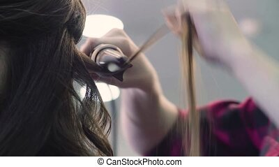 Close up. Hands of stylist curling hair with curling tongs