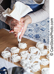 hands of the chef with confectionery bag cream to parchment paper at pastry shop kitchen