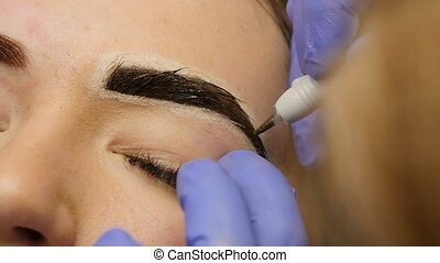 close-up hands of the master doing brows tattoo. permanent...