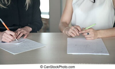 Close up hands of women discussing business with documents in office