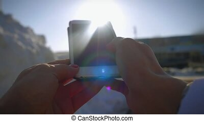 Close Up hands of young woman using a smartphone in winter on the sun and sky background
