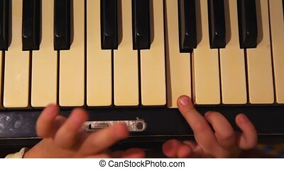 close up hands pressing keys of piano one finger of girl which plays it and sings