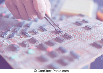 close up hands reapair the electric board with tweezers f