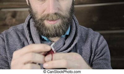close-up hands with knitting needles, bearded man trying to knit