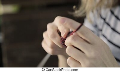 close-up hands with knitting needles, beautiful woman knits