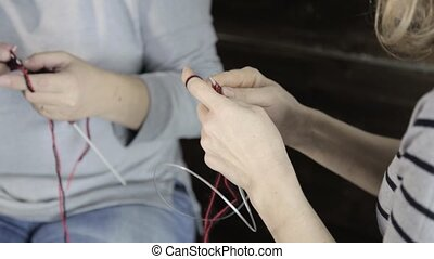 close-up hands with knitting needles, old woman knits and...