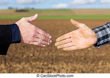 Close up Handshake between businessman and farmer