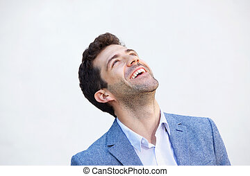 Close up handsome young man laughing against white background