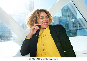 Close up happy african american business woman talking on mobile phone in city