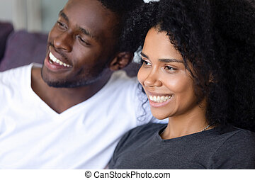 Close up happy African American couple sitting together on sofa