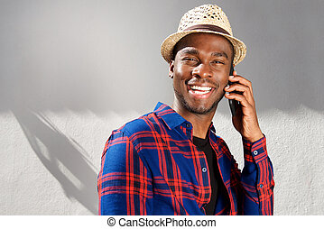 Close up happy african american man with hat talking with cellphone by white wall