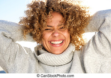Close up happy african american woman laughing with hands behind head