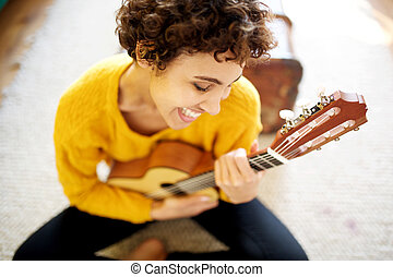 Close up happy african american woman smiling with guitar