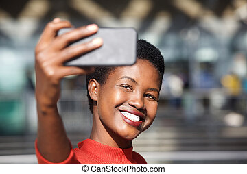 Close up happy african american woman taking selfie with mobile phone camera