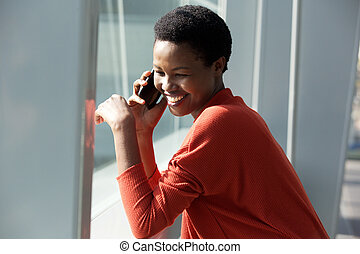 Close up happy african american woman talking with cellphone by window