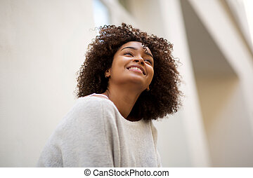 Close up happy african american woman with curly hair smiling outside