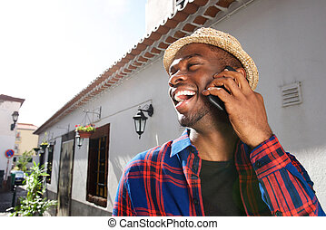 Close up happy african american young man talking with cellphone outside