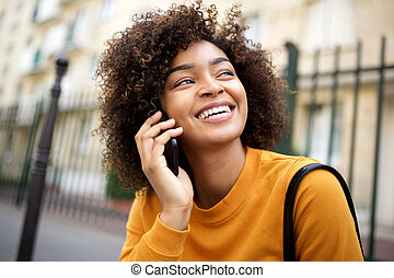 Close up happy african american young woman talking with cellphone outside in city