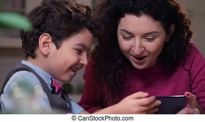 Close up happy mom and son watching funny video