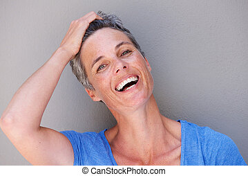 Close up happy older woman laughing with hand in hair