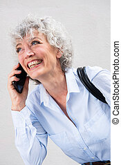 Close up happy older woman talking with mobile phone