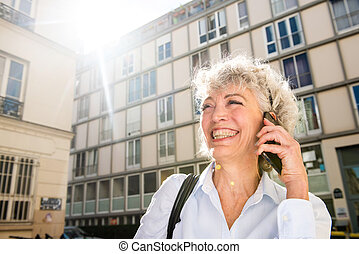 Close up happy older woman talking with mobile phone in city