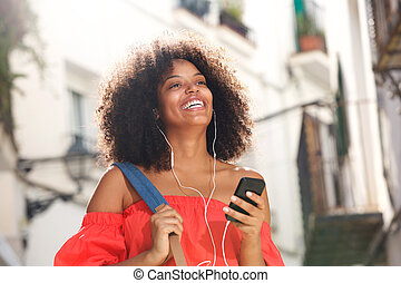 Close up happy woman on street with headphones and smart phone