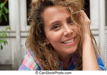 Close up happy woman smiling with hand in curly hair