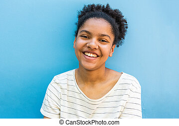 Close up happy young african american girl by blue background