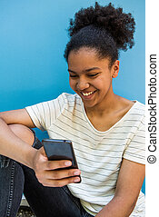 Close up happy young african american girl sitting by blue background looking at mobile phone