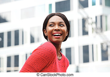 Close up happy young african american woman laughing in the city