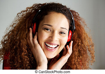 Close up happy young african american woman smiling and listening to music with headphones