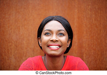 Close up happy young african american woman smiling and looking up