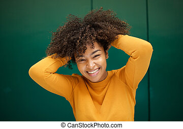 Close up happy young african american woman smiling with hands in curly hair