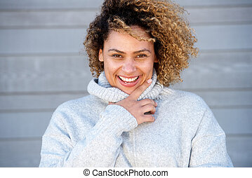 Close up happy young african american woman with curly hair in warm sweater