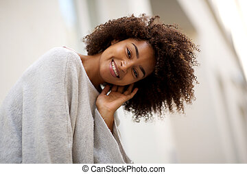 Close up happy young african american woman with curly hair smiling outside