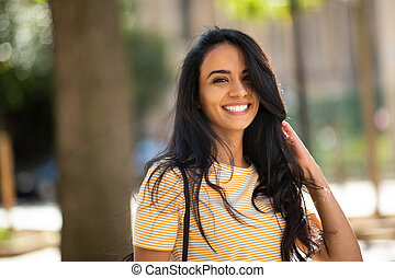 Close up happy young arabic woman smiling with hand in hair outside