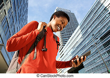 Close up happy young black woman walking in city and looking at mobile phone