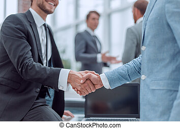 happy young businessman shaking hands with his business partner