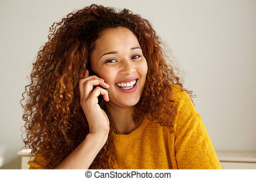 Close up happy young mixed race woman smiling and talking on cellphone
