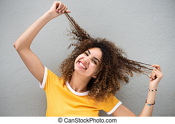 Close up happy young woman holding curly hair in hand