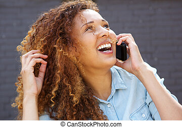 Close up happy young woman laughing and talking on mobile phone