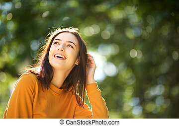 Close up happy young woman laughing in park with hand in hair