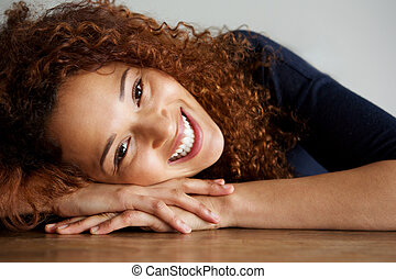 Close up happy young woman leaning on desk and smiling